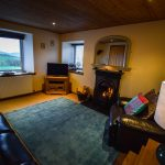 The spacious lounge with open fire at Gables Cottage, Polbain
